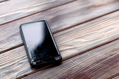 Ð¡loseup black smartphone with broken screen glass lying on wooden table. Concept of dropping phone, broken gadget, electronics. Ð¡loseup black smartphone stock photo