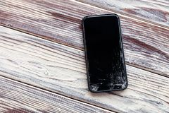 Ð¡loseup black smartphone with broken screen glass lying on wooden table. Concept of dropping phone, broken gadget, electronics. Ð¡loseup black smartphone stock photos