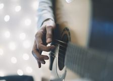 Ð¡loseup of a man playing the guitar in a homelike atmosphere, sitting in a chair against a background of bokeh light horizontal royalty free stock image
