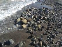 Сobblestones sunbathe on the shore royalty free stock image