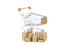 Ð¡oins in a column on the background shopping cart on white. Royalty Free Stock Photography
