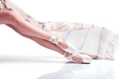 Ballerina feet pointe and with silk scarf on white background royalty free stock photography