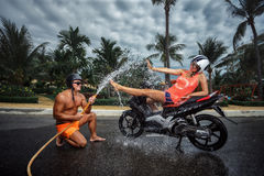 Ð¡ouple having fun with garden hose splashing summer rain. Portrait of couple having fun with garden hose splashing summer rain on scooter stock images