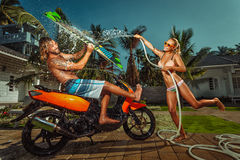 Ð¡ouple having fun with garden hose splashing summer rain. Portrait of glamorous young couple having fun with garden hose splashing summer rain on scooter royalty free stock images