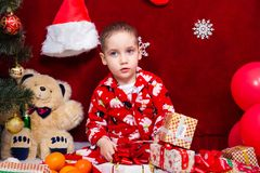 Сute baby in pajamas parses Christmas presents Royalty Free Stock Photo