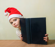 Сute girl in Santa Claus hat with big blue book. Royalty Free Stock Images