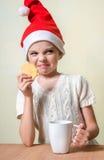Сute girl in Santa Claus hat eat cookies. Royalty Free Stock Image