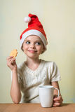 Сute girl in Santa Claus hat eat cookies. Royalty Free Stock Photo