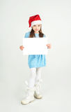 Сute girl in Santa Claus hat with a white blank paper sheet. С Royalty Free Stock Photo