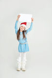 Сute girl in Santa Claus hat with a white blank paper sheet. С Royalty Free Stock Images