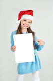 Сute girl in Santa Claus hat with a white blank paper sheet. С Royalty Free Stock Photography