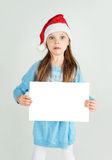 Сute girl in Santa Claus hat with a white blank paper sheet wit Royalty Free Stock Image