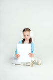 Сute girl in winter clothes with a white blank paper sheet. Stock Photography