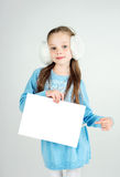 Сute girl in winter clothes with a white blank paper sheet Royalty Free Stock Photos