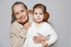 Ð¡ute gray long haired grandmother in knitted sweater hugs granddaughter with chicken pox, white dots, blisters on face. Concept. Family photo session stock image