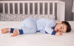 Ð¡ute little baby boy in light blue pajamas sleeping peacefully on bed at home. stock photography
