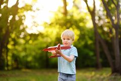 Ð¡ute little boy playing with toy airplane in the sunny park stock photo