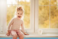 Ð¡ute little kid girl in pajama sitting by big window playing smiling enjoying home. Cacao cup standing on window. Autumn Season. Interior Family Textile stock image