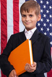 Ð¡ute schoolboy is holding a book against USA flag royalty free stock images