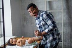 Эмоциональный нервный устрашенный папа изменяет его пеленку младенца, фото конца-вверх стоковое изображение