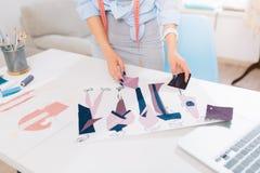 Это изображение описывает процессы конструировать одежды в мастерской Руки искать девушки стоковые фото