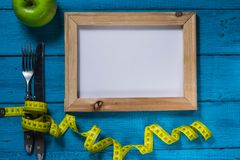 Яблоко и лента сантиметра на покрашенной предпосылке с космосом для текста, взгляда сверху спорт концепции, диета, фитнес, план,  стоковое фото