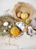 Яйца и яйца триперсток в пакете, тыквы, сено, концепция пасхи, подготовка на праздник, сбор, сезонные праздники стоковое фото