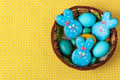 Яйца кроликов пряников пасхи, желтых и голубых цыпленка и триперсток в плетеной корзине, взгляде сверху стоковая фотография