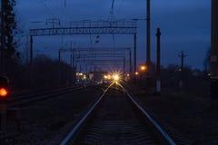 Яркий прожектор блесков поезда прямо в глаза в вечере стоковое изображение rf
