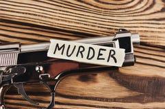 УБИЙСТВО надписи на сорванной бумаге и лоснистом пистолете стоковые изображения rf