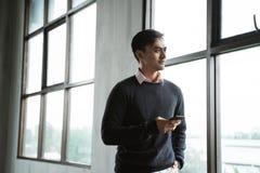 Уверенный молодой бизнесмен используя сотовый телефон стоковое изображение rf