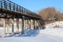 Узкий пешеходный мост на ходулях над промоиной в зиме пересекая реку стоковая фотография