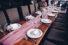 Украшения свадьбы Таблица украшенная с розовой тканью стоковое изображение