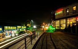 Улица ночи в туристском лыжном курорте Bukovel Светя окна и проходить автомобили стоковое изображение