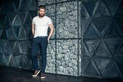 Ультрамодный взгляд Во всю длину красивого молодого человека смотря отсутствующий и держа руки в карманн пока стоящ против серой  стоковая фотография rf