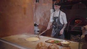 Умелый создатель пиццы варит тесто на современной кухне ресторана за стеклом Молодой парень в форме шеф-повара устанавливая пиццу акции видеоматериалы