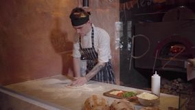 Умелый создатель пиццы варит тесто на современной кухне ресторана за стеклом Молодой парень в форме шеф-повара закручивая и акции видеоматериалы