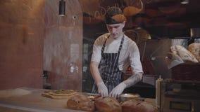 Умелое pizzaiolo варит пиццу на современной кухне ресторана за стеклом Молодой парень в установке формы шеф-повара акции видеоматериалы