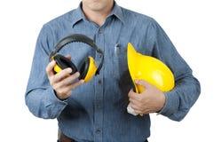 Умный работник инженера нести голубую рубашку и придержать желтый шлем безопасности и желтые халявы уха на предпосылке изолята стоковая фотография rf
