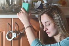 Унылая и утомленная девушка надеванная наручники к счетчику кухни с много стоковое изображение rf