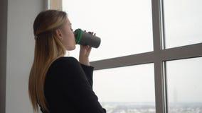 Удерживание молодой женщины дизайнерское в кофейной чашке руки выпивая на предпосылке окна сток-видео