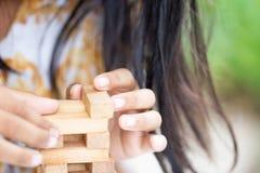Удерживание руки девушки/игра деревянного блока стоковые фотографии rf