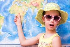 Удивленная девушка в шляпе и шоу солнечных очков на карте мира стоковые изображения