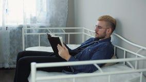 Удовлетворенный молодой привлекательный человек со стеклами и желтыми волосами читая книгу пока кладущ в кровать дома акции видеоматериалы