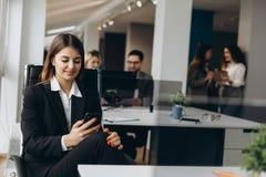 Усмехаясь бизнес-леди используя сотовый телефон с коллегами на предпосылке в офисе стоковое изображение