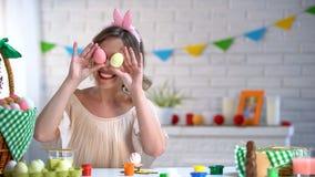 Усмехаясь женщина имея потеху, держа красочные пасхальные яйца около ее глаз, шутка стоковая фотография