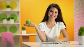 Усмехаясь красивая дама держа таблицу зеленой руки яблока сидя, здравоохранение, диету видеоматериал