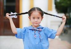 Усмехаясь маленький азиатский ребенок в школьной форме держа ее 2 связанных волоса ponytails стоковые изображения rf
