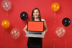 Усмехаясь молодая женщина в черный праздновать платья, держа компьютер ПК ноутбука с пустым черным пустым экраном на ярком красно стоковое фото rf