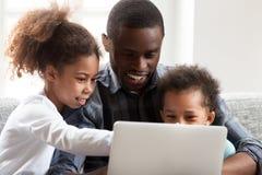 Усмехаясь молодая черная игра папы на ноутбуке с детьми стоковые изображения rf